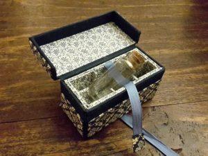 Doosje voor speciale inhoud: met een speciaal lintje wordt het flesje (6 cm) uit het doosje gehaald